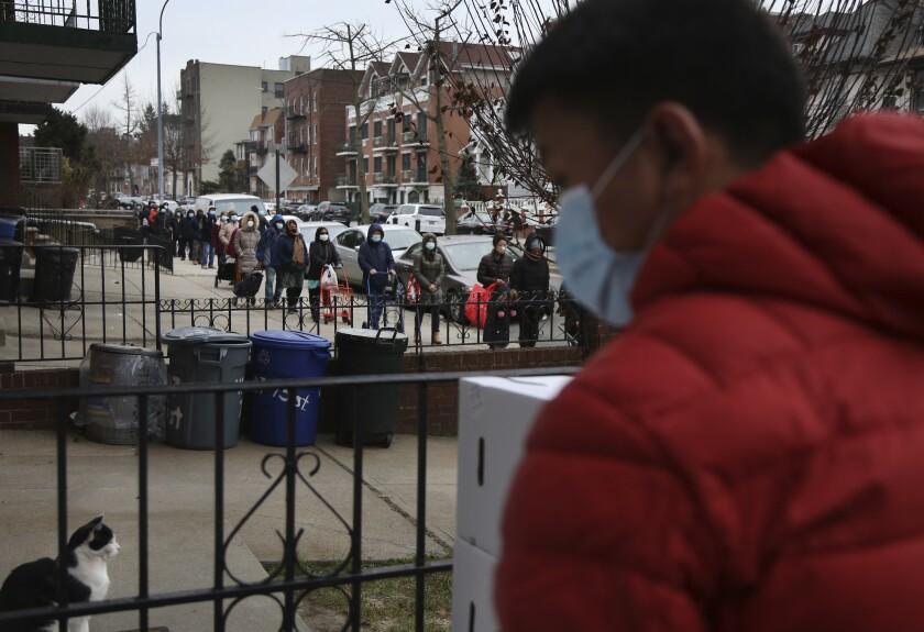 Personas formando una fila de dos manzanas de largo para recibir una despensa gratuita