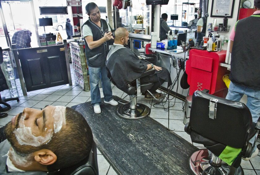 Javiel Rodriquez, center, owner of Knockout barbershop, shaves the head of a customer while another waits with shaving cream, Thursday, Jan. 8, 2015, in New York. Dirty nail clippers could get the same treatment as spoiled food under a proposal to expand New York City's restaurant letter-grade syst