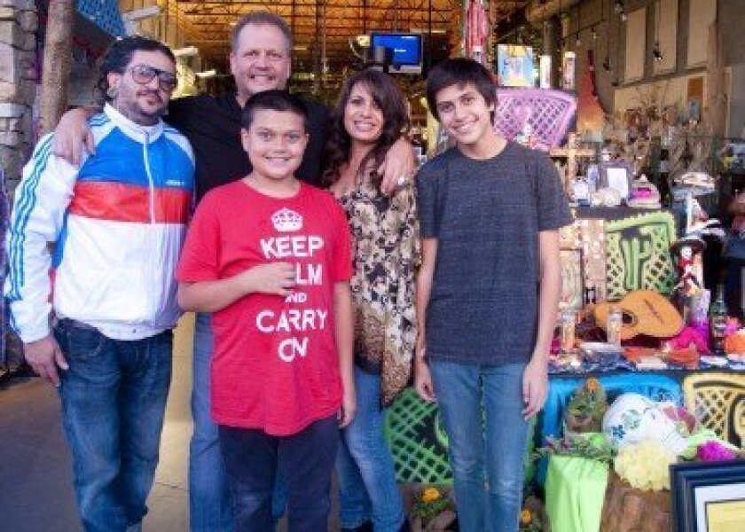 Artist Todd Swenke (right) stands by his altar with his family, Carla, Quentin and Todd Jr. and musician Karlos Paez (left). Photo/Claire Harlin