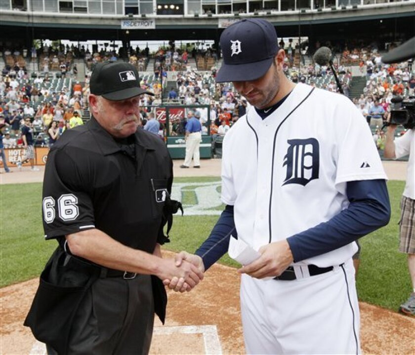 Home plate umpire Jim Joyce, left, shakes hands with Detroit Tigers pitcher Armando Galarraga while handing the lineup card on the field before the Detroit Tigers-Cleveland Indians MLB baseball game in Detroit, Thursday, June 3, 2010. Galarraga lost his bid for a perfect game with two outs in the ninth inning on a disputed call at first base by Joyce on Wednesday night. (AP Photo/Paul Sancya)