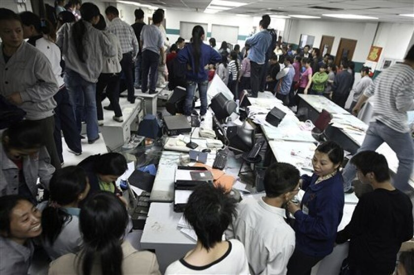 In this Nov. 25, 2008 file photo, factory workers occupy an office after smashing equipment during a protest at the Kaida toy factory over a labor dispute in Dongguan, east China's Guangdong province. The growth rate for China's industrial output fell further in November as exports plunged, adding to the threat of heavy job losses that could fuel unrest, data showed Monday, Dec. 15, 2008. (AP Photo/Color China Photo, File)