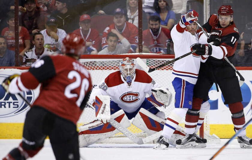Arizona Coyotes' Michael Stone, left, sends the puck at Montreal Canadiens' Mike Condon, second from left, for a score as Coyotes' Martin Hanzal (11), of the Czech Republic, and Canadiens' Alexei Emelin, second from right, battle for position during the first period of an NHL hockey game Monday, Fe