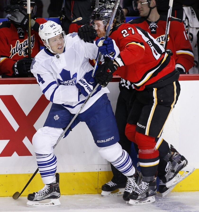 Toronto Maple Leafs' Peter Holland, left, is hit by Calgary Flames' Dougie Hamilton during first period NHL action in Calgary, Alberta, Tuesday, Feb. 9, 2016. (Larry MacDougal/The Canadian Press via AP) MANDATORY CREDIT