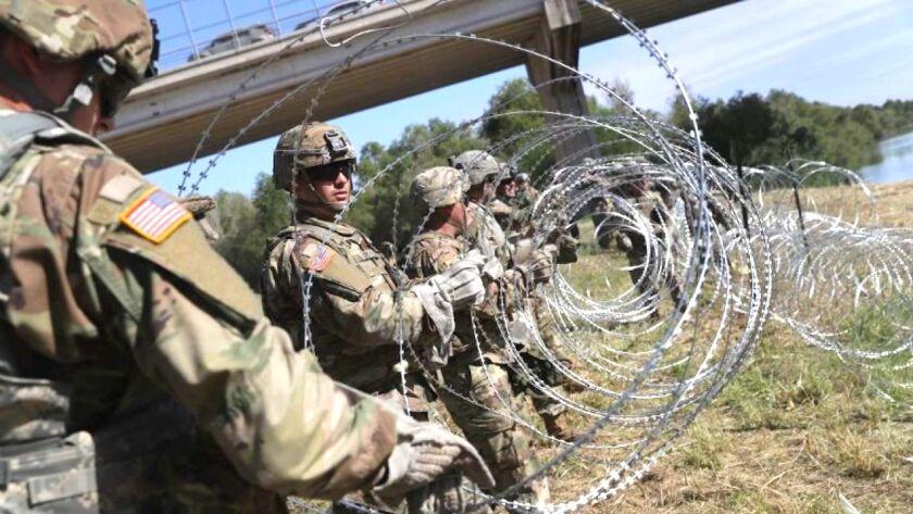 Soldados de Estados Unidos colocan alambre de púas en el llímite fronterizo con México.