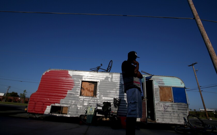 A man stands outside his battered trailer along Broadway in an unincorporated section of southern L.A. County. Shortly afterward, he was arrested for outstanding warrants and his home was towed away.