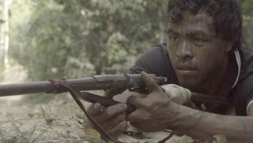 """In this Sept. 2019, video frame, Paulo Paulino Guajajara, a Forest Guardian protecting the Arariboia indigenous reserve poses with his makeshift weapon, at the reserve in Maranhao state, Brazil. The 26-year-old Guajajara was killed in an ambush by illegal loggers on Friday, Nov. 1, 2019. """"My son fought and died. He died for all of us here, defending this area,"""" Paulo's father Ze Maria Paulino Guajajara said. (Documentary Iwazayzar - Guardioes da Natureza via AP)"""