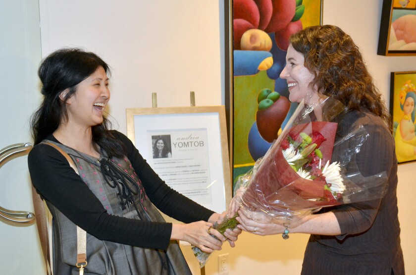 Artist Andrea Yomtob, left, is congratulated by her former Nickelodeon colleague Amy Casler during the Friday evening opening of her exhibit at Gallery 839.