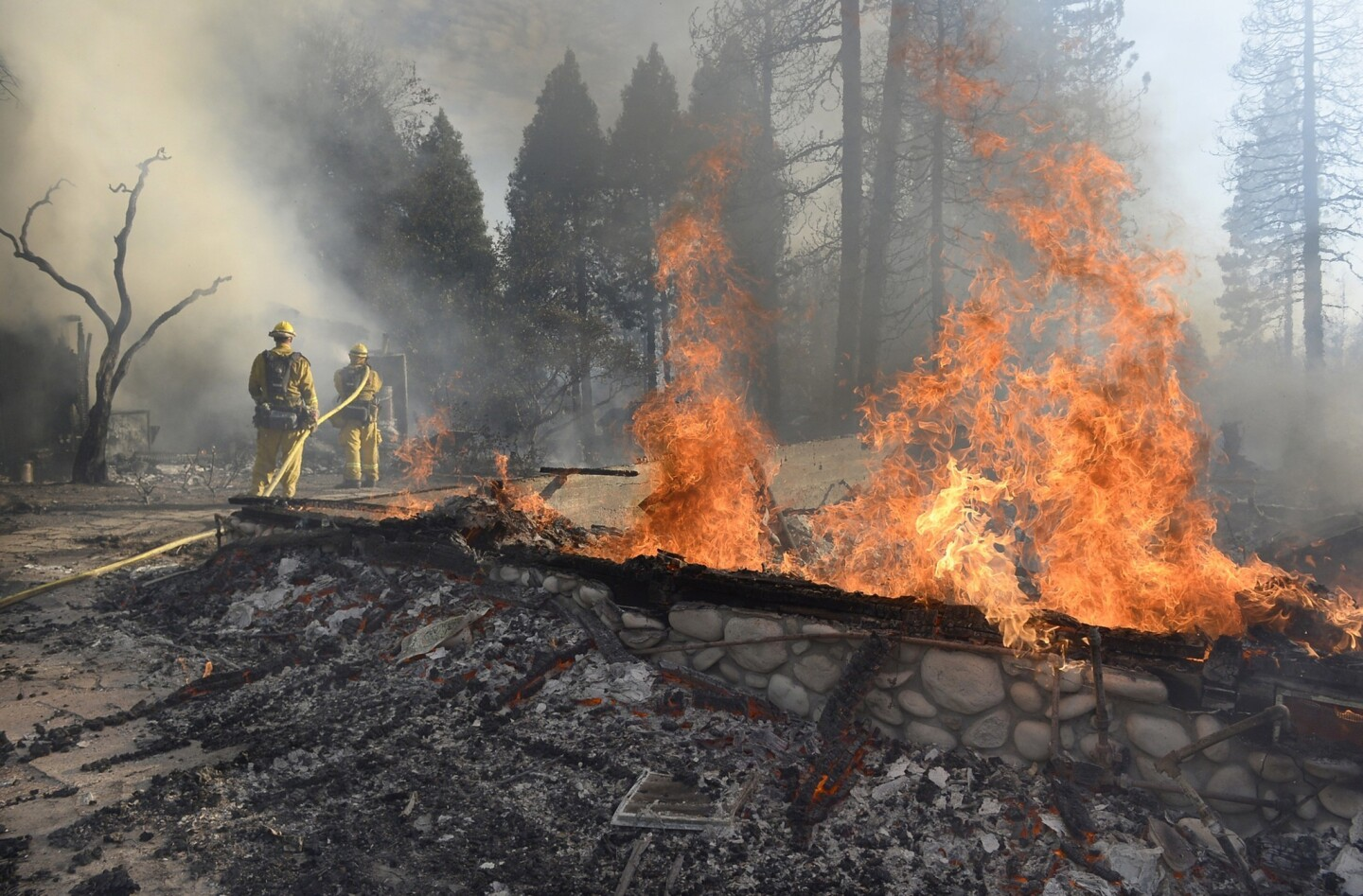 Firefighters douse flames from an outbuilding on Cedar Drive in Oakhurst, Calif., on Sunday.