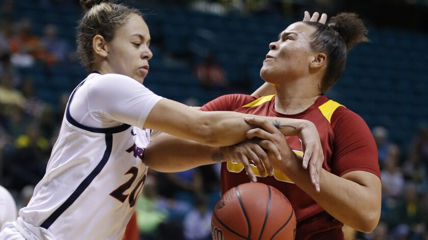 Arizona's Dominique McBryde, left, fouls USC's Kayla Overbeck during the first half at the Pac-12 women's tournament on Thursday in Las Vegas. (AP Photo/John Locher)