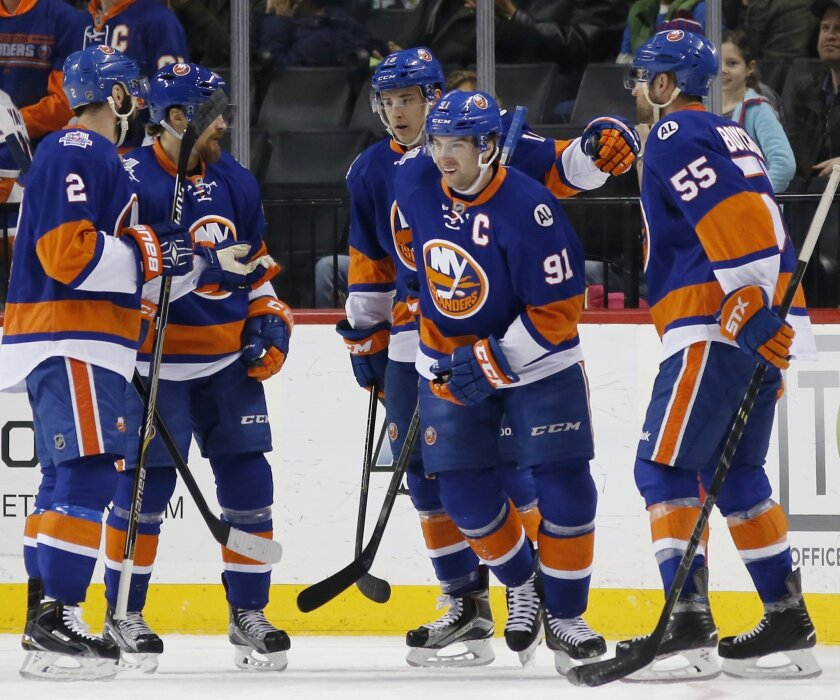 New York Islanders celebrate with center John Tavares (91) who scored one of three goals in the first period of an NHL hockey game against the Edmonton Oilers in New York, Sunday, Feb. 7, 2016. New York Islanders defenseman Johnny Boychuk (55) also scored in the first. (AP Photo/Kathy Willens)