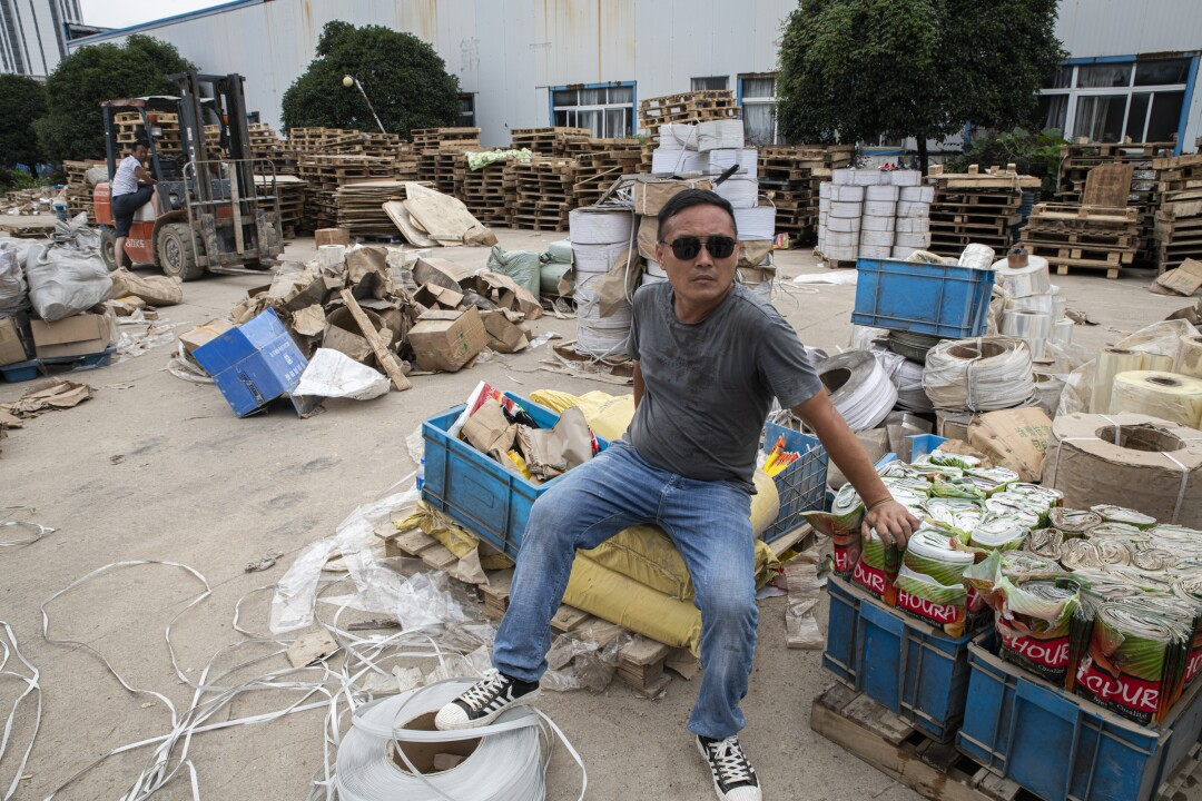 Ma Dacong sits among flooded factory gear to be disposed of at a tea factory in Shexian.