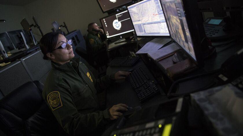 U.S. Border Patrol agents monitor security footage at a facility in Nogales, Ariz.