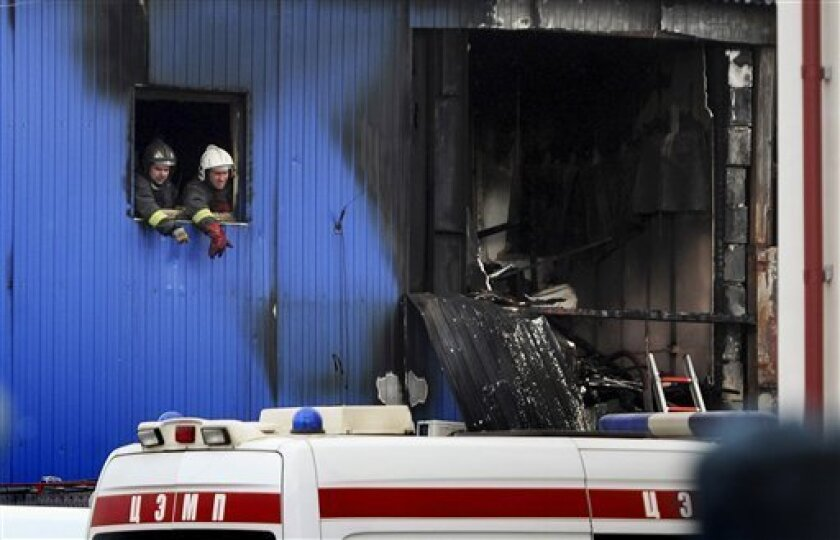 Firefighters and Emergency Ministry officers examine the scene of a fire at Kachalovo construction market on Tuesday, April 3, 2012. A blaze at a market on the outskirts of Moscow on Tuesday killed 15 migrant workers sleeping in a metal shed on the premises, the city fire department said. All were citizens of former Soviet nations in Central Asia. (AP Photo/ Maxim Dmitriyev)