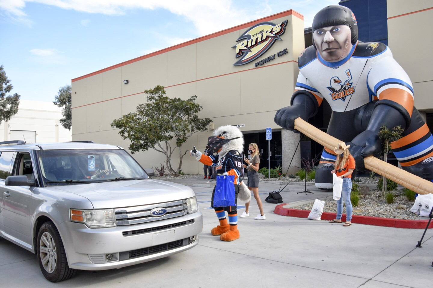 Gulliver the mascot greets a carload of fans outside The Rinks.