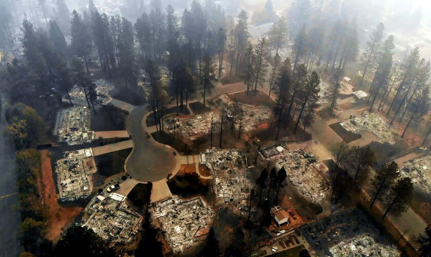 Aerial view of a block of destroyed homes and charred trees with smoke lingering in the sky