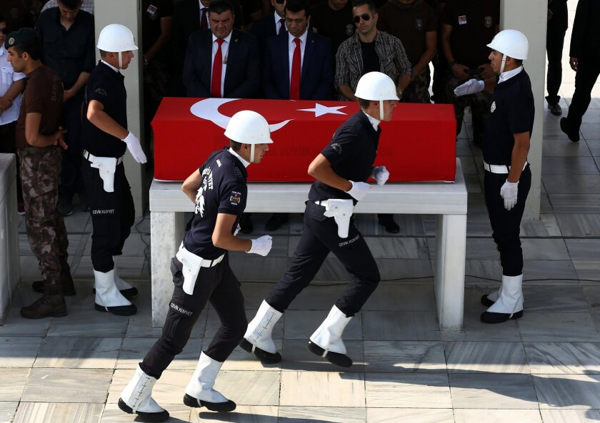 A Turkish honor guard runs in front the coffin of a policeman during his funeral procession, in Ankara, Turkey, Wednesday, July 20, 2016. Turkey on Wednesday intensified a sweeping crackdown on the media, the military, the courts and the education system following an attempted coup, targeting tens of thousands of teachers and other state employees for dismissal in a purge that raised concerns about basic freedoms and the effectiveness of key institutions. (AP Photo/Hussein Malla)