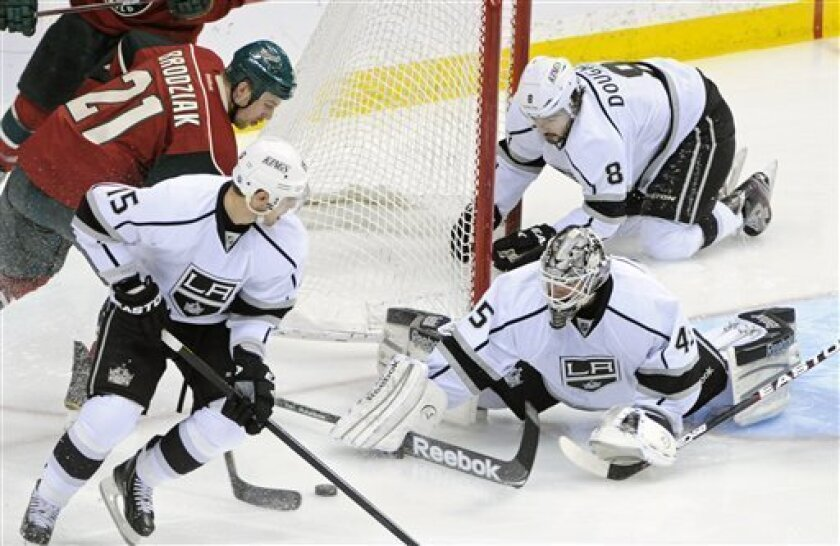 Los Angeles Kings' Drew Doughty (8) dislodges the net as Kings goalie Jonathan Bernier, bottom right, reaches to stop a scoring-attempt by Minnesota Wild's Kyle Brodziak (21) in an NHL hockey game on Saturday, March 31, 2012, in St. Paul, Minn. (AP Photo/ Jim Mone)