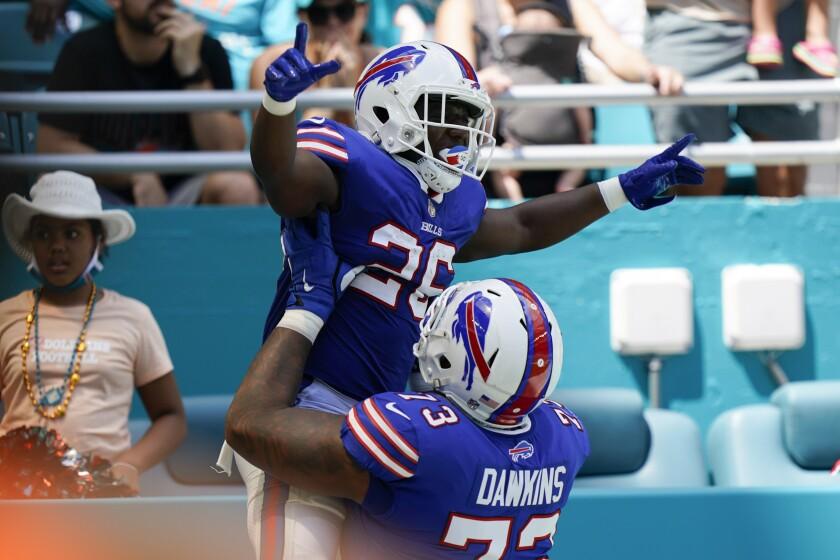 El running back Devin Singletary (26) de los Bills de Buffalo es alzado por el tackle ofensivo Dion Dawkins (73) tras anotar un touchodown, el domingo 19 de septiembre de 2021. (AP Foto/Wilfredo Lee)