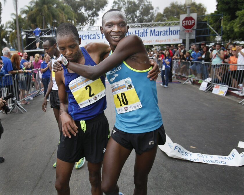Nelson Oyugi of Kenya (10), the race winner, holds onto friend and second place finisher Ernest Kebenei, left, of Kenya at the finish line Sunday. The running of the 36th annual America's Finest City half marathon and 5K saw a field of 10,000 runners enjoying cool, overcast conditions for the race that wound its way from the Cabrillo National Monument along Harbor Drive, through downtown and over the bridge into Balboa Park to finish in front of the Hall of Champions. All three male finishers in the AFC Half ran times that beat the existing course record. Participants came from 14 countries and 45 different states in the U.S. to run in both races.
