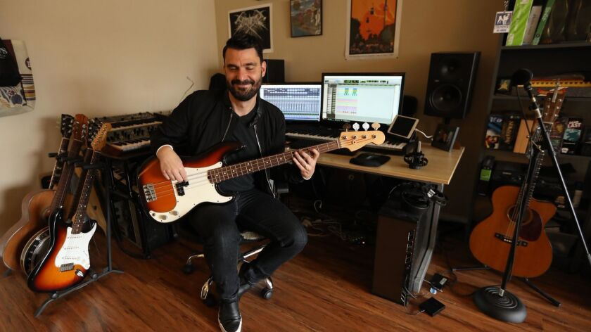 LOS ANGELES, CA - SEPTEMBER 28, 2018 - TV and film composer Ryan Elder plays his bass in the studio