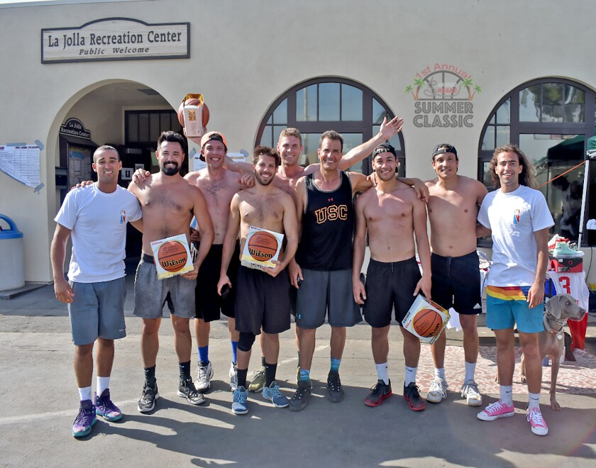 Team members from Crushin' Dreams, 2018 winners of the inaugural Summer Classic, are presented with Sneaks-branded basketballs by tournament co-founders Sawsun Khodapanah and Tyson Young at La Jolla Rec Center.
