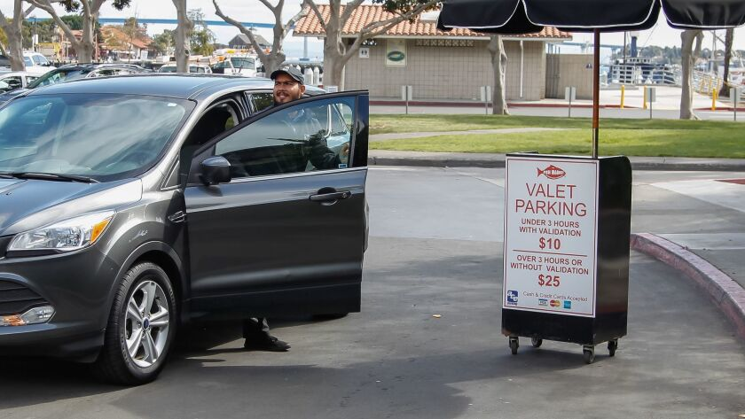 A valet steps out of a car in downtown San Diego. Valets and parking lots are seeing less business as people use ride-hailing services more.