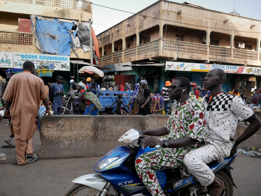Men ride a motorbike past Dabanani market in central Bamako, Mali on March 8, 2019