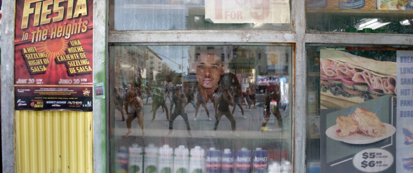 A man looks through the reflection in a glass window.