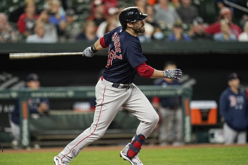 Boston Red Sox designated hitter J.D. Martinez watches his ball as he hits a solo home run off Baltimore Orioles starting pitcher Zac Lowther during the second inning of a baseball game, Wednesday, Sept. 29, 2021, in Baltimore. (AP Photo/Julio Cortez)