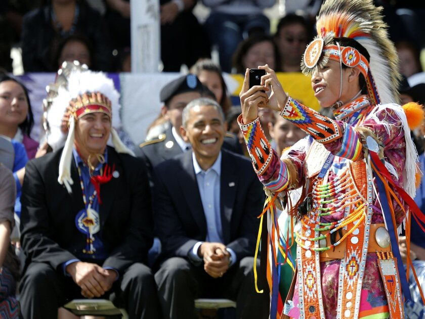 A Native American dancer creates a selfie with President Barack Obama and Chairman if the Standing Rock Sioux Tribe David Archambault, left, on the Standing Rock Indian Reservation Friday, June 13, 2014, photo in Cannon Ball, N.D. President Obama is making his first presidential visit to Indian Country for a look at two sides of Native American life, a celebration of colorful cultural traditions on the powwow grounds and a view of the often bleak modern-day conditions on tribal lands. (AP Photo/Charles Rex Arbogast)
