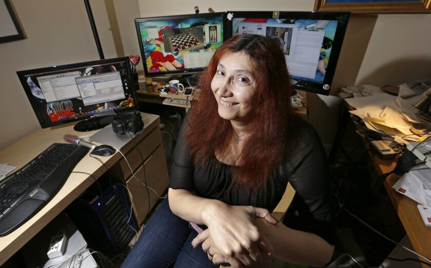 "In this Tuesday, Dec. 16, 2014, photo, longtime video game developer Becky Heineman poses for a photo at her workspace in Seattle. In the male-dominated world of multiplayer online games like ""Grand Theft Auto,"" ""Halo,"" and ""Call of Duty,"" many women say they've had to take drastic steps to escape"