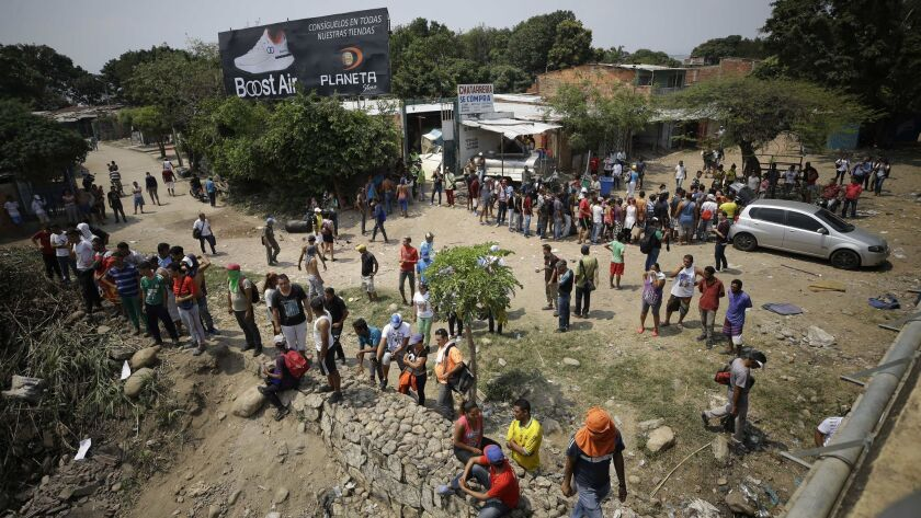 Venezuelan migrants wait for food being handed out by Colombian residents as others try to clear a roadblock created by Venezuelan security forces at the Simon Bolivar International Bridge near Cucuta, Colombia, on the border with Venezuela, on Sunday.