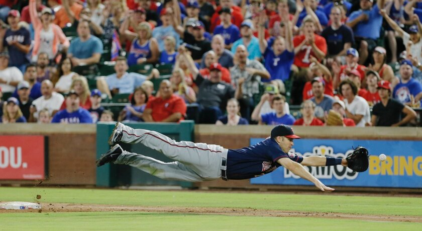 Minnesota Twins first baseman Joe Mauer dives for a bad throw from second baseman Brian Dozier during the second inning of a baseball game against the Texas Rangers on Saturday, July 9, 2016, in Arlington, Texas. Mauer was unable to make the catch and the ball went out of play. (AP Photo/Brandon Wa
