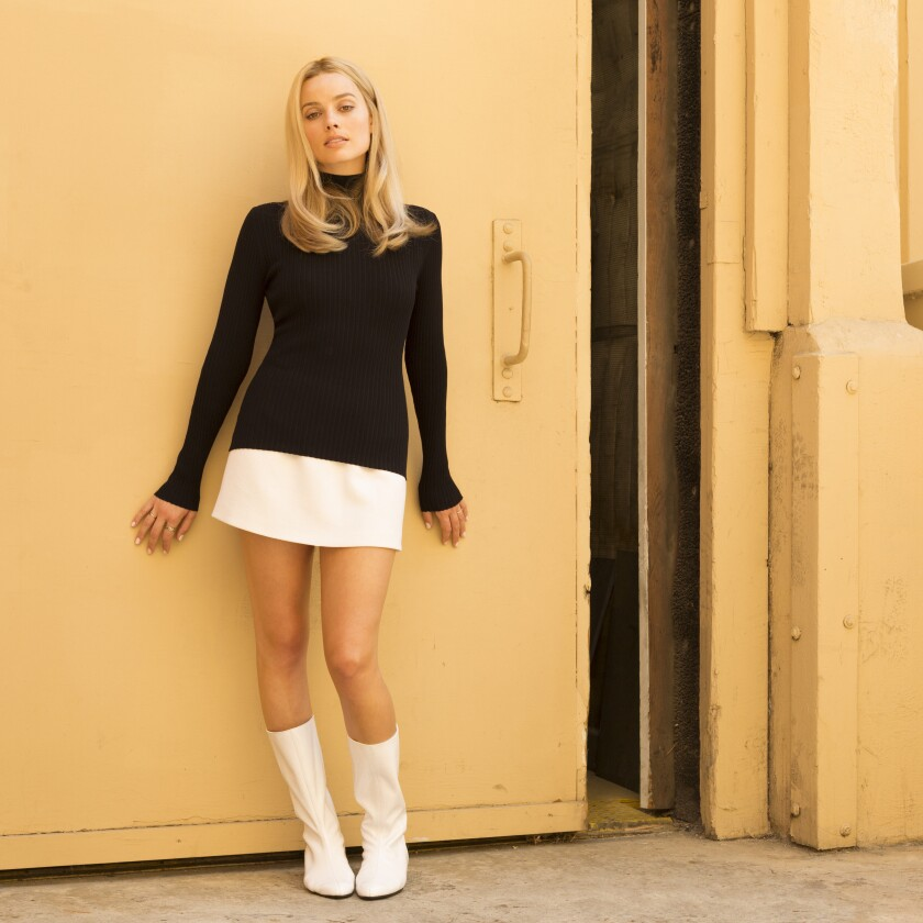 Margot Robbie as Sharon Tate, wearing a black turtleneck, white mini-skirt and white go-go boots.