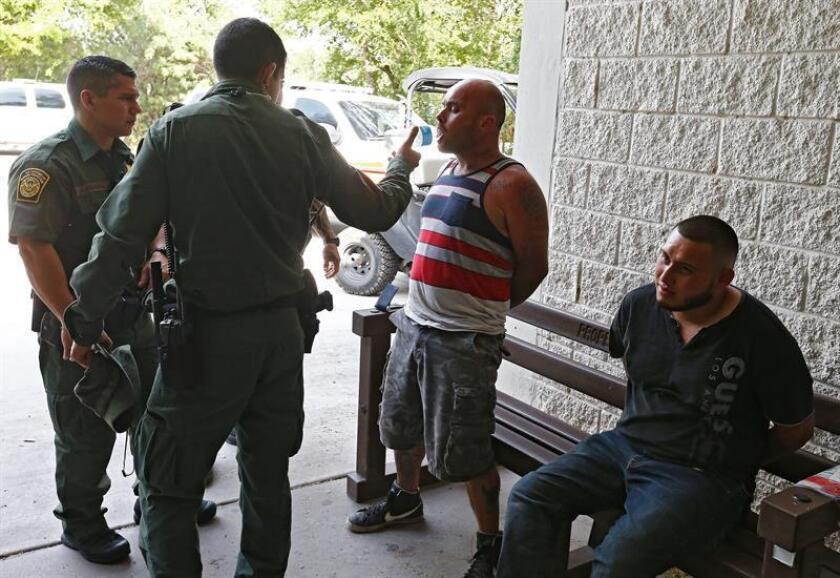 Un agente de la Patrulla Fronteriza de Estados Unidos (USBP) da de beber a un hombre esposado tras ser detenido sospechoso de haber cruzado el Río Grande para pasar ilegalmente la frontera con los Estados Unidos cerca de McAllen en Texas (Estados Unidos. EFE/Archivo