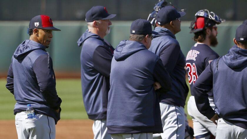 An injured Cleveland Indians' Francisco Lindor stands outside a team huddle at the Indians spring tr
