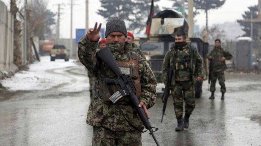 Afghan soldiers stand guard at the entrance to a military academy that was attacked Monday in Kabul.