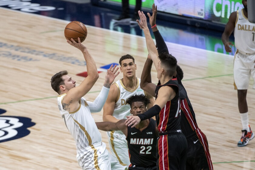 Dallas Mavericks guard Luka Doncic, left, shoots over Miami Heat's Tyler Herro (14) and Bam Adebayo, obscured, as Miami's Jimmy Butler (22) and Dallas' Dwight Powell watch during the first half of an NBA basketball game Friday, Jan. 1, 2021, in Dallas. (AP Photo/Jeffrey McWhorter)