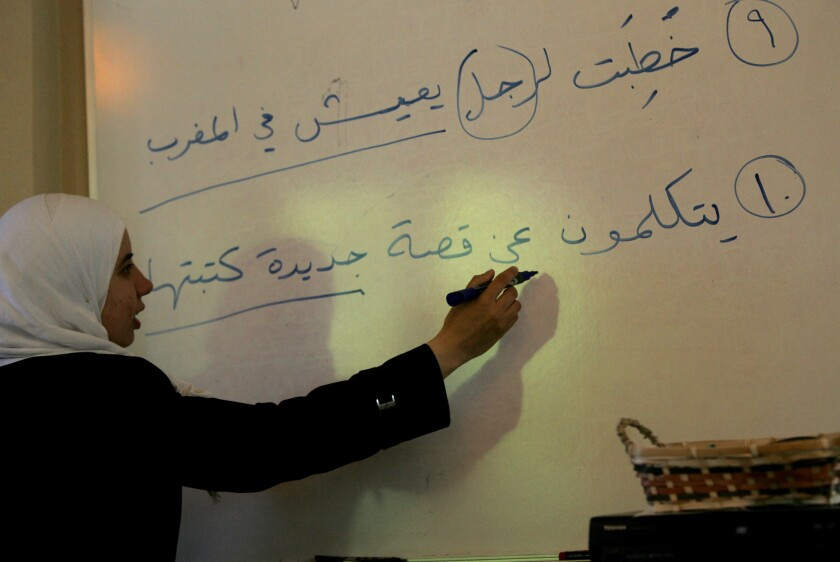 Professor Nawar Taleb-Agha writes a sentence on a whiteboard for Zaytuna students in Berkeley who are taking an intensive study of Arabic.