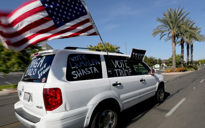 A supporter of President Trump drives through Redding on Oct. 24.