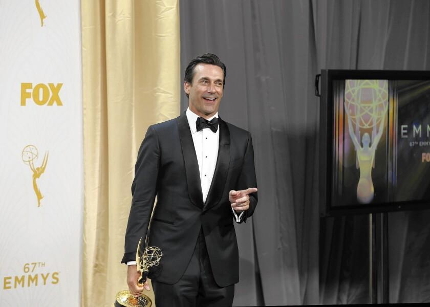 Jon Hamm keeps a tight grip on his first Emmy Award.
