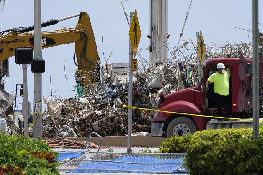 Un trabajador espera para cargar su camión con escombros del derrumbe del edificio de apartamentos