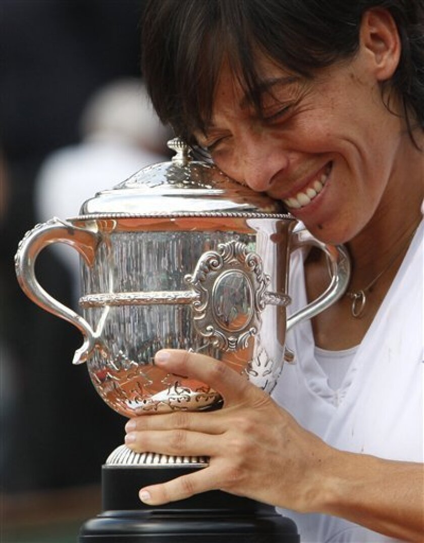 Italy's Francesca Schiavone smiles while holding her cup after defeating Australia's Samantha Stosur in the women's final match of the French Open tennis tournament at the Roland Garros stadium in Paris, Saturday, June 5, 2010. (AP Photo/Michel Euler)