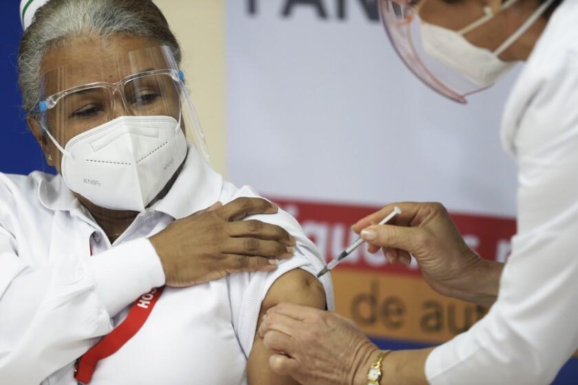 La enfermera Violeta Gaona, de 59 años, recibe una inyección de la vacuna Pfizer-BioNTech para COVID-19