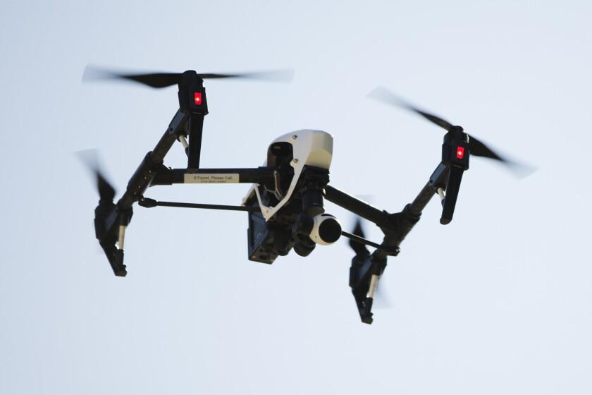 ARCHIVO - En esta foto, un dron toma video y fotografías de un edificio de apartamentos en Filadelfia. Funcionarios federales de aviación en los Estados Uidos dicen que hay tantas personas registrando drones y solicitando licencias de pilotaje de drones que en el futuro pudiera haber millones de esos aparados en los cielos del país. (AP Foto/Matt Rourke)