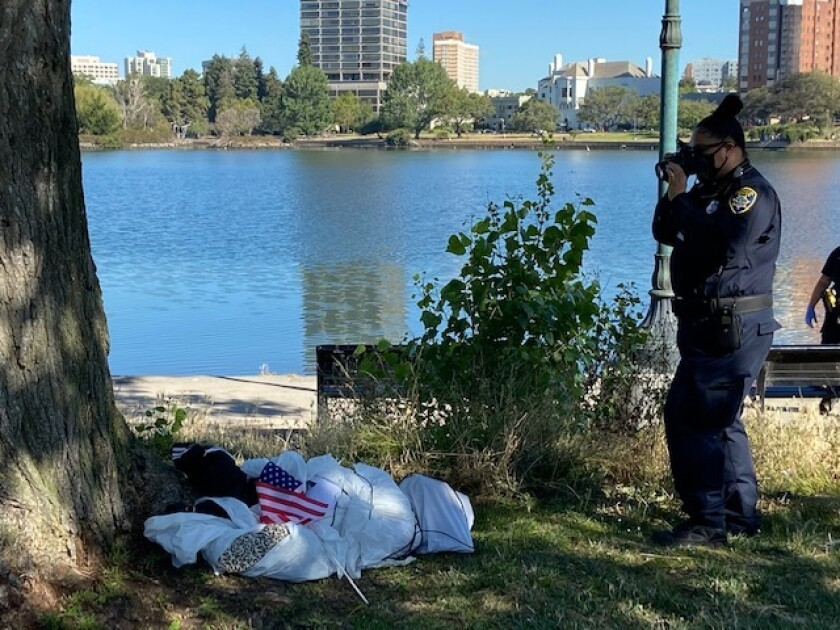 A police officer takes a photo of a figure that was hanging in effigy from a tree near Lake Merritt in Oakland