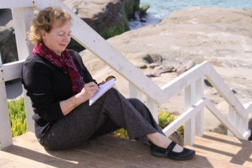 Kay Sanger jots down some thoughts at WindanSea beach.  Courtesy