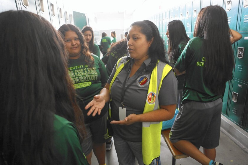 Supervisor aide Maria Melendrez talks with students in the girls locker room at Nava College Preparatory Academy. Melendrez was one of the parents who spearheaded the school's founding.
