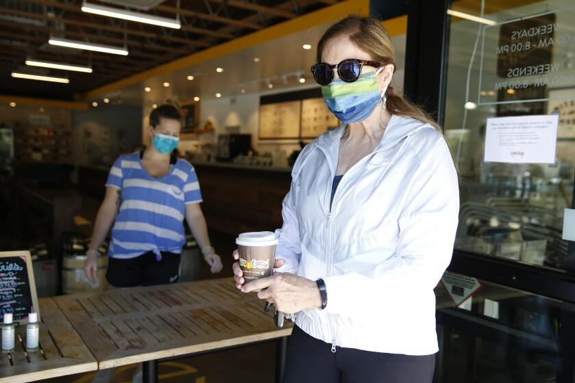 Barbara Meier, right, wears a face mask as picks up her drink order from Philz Coffee in Davis, Calif., Monday, April 27, 2020. Yolo County, where Davis is located, now requires people to wear face masks in public. Face coverings are not required at home, alone in a car, outdoors, walking, hiking bicycling or running. (AP Photo/Rich Pedroncelli)