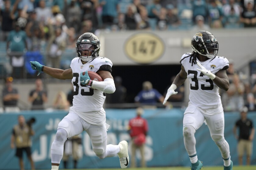Jacksonville's Jamal Agnew (39) returns a kickoff for a touchdown as running back Dare Ogunbowale (33) follows him.